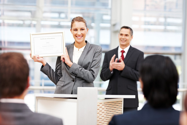Business, Caucasian, Male, Sitting, Cheerful, Happiness, Adult, People, Men, Smiling, Female, Beautiful, Confidence, Well-dressed, Women, Young Adult, Young Women, Businesswoman, Professional Occupation, Expertise, Suit, White Collar Worker, Success, Adults Only, Office Worker, Showing, Waist Up, Selective Focus, Horizontal, Presentation, Convention Center, Conference, Meeting, Businessman, Award, Stage, Audience, Business Person, Podium, Small Group Of People, Group Of People, Attractive Female, Over The Shoulder View, 30s, Certificate, Awards Ceremony